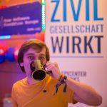 """Ein Bild von eest9 wie er vor einem epicenter.works Aufsteller am 36c3 aus einer """"eest9""""-Tasse Kaffee trinkt."""